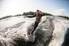 Free Active Male Surfer Riding Foaming River Wave From Motorboat Stock Photography - 195278422
