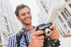 Active male tourist looking at photos. Happy young man is watching done shots with touristic places. He is holding camera and laughing. Traveler in standing on Royalty Free Stock Photo
