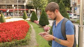 Active male urban resident checking mobile app on smartphone, big city lifestyle. Stock footage stock footage