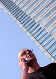 Active man. Casual man speaking to the mobile phone near a skyscraper in a big city Royalty Free Stock Photos