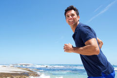 Active man casually running at the beach. Portrait of an active man casually running at the beach Royalty Free Stock Image