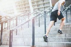 Active man climbing up the stairs in a sportswear. Move on. Active enthusiastic athletic man wearing sportswear and climbing up the stairs before training Stock Photo