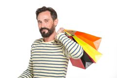 Active man with colorful paper bags isolated on white. Man in navy slip-over carrying shopping bags. Smiling happy man and bags. Handsome man with colorful paper Royalty Free Stock Photos