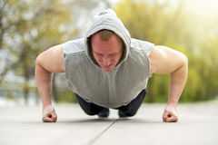 Active man doing push up in park. Stock Image