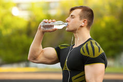 Active man drinking water from a bottle, outdoor. Muscular male quenches thirst Stock Images