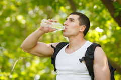 Active man drinking water from a bottle, outdoor. Young muscular male quenches thirst.  royalty free stock photos
