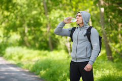 Active man drinking water from a bottle, outdoor. Young muscular male quenches thirst Stock Image