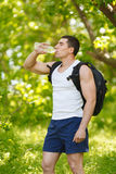 Active man drinking water from a bottle, outdoor. Young muscular male quenches thirst Stock Photo