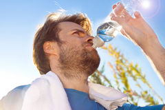 Active man drinking water after outdoor workout Stock Images