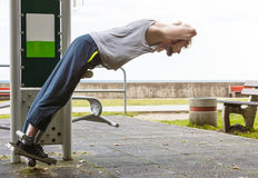Active man exercising on backtrainer outdoor. Royalty Free Stock Photography