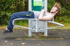 Active man exercising on bench outdoor. Stock Photos