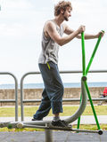 Active man exercising on elliptical trainer. Royalty Free Stock Images