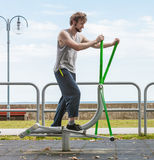 Active man exercising on elliptical trainer. Royalty Free Stock Photo