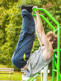 Active man exercising on ladder outdoor. Active young man exercising on ladder. Muscular sporty guy in training suit working out at outdoor gym. Sport fitness Stock Photos