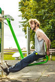 Active man exercising on leg press outdoor. Stock Photo