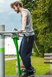 Active man exercising on ski trainer outdoor. Active young man exercising on ski trainer machine. Muscular sporty guy in training suit working out at outdoor Stock Photo