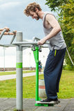 Active man exercising on ski trainer outdoor. Active young man exercising on ski trainer machine. Muscular sporty guy in training suit working out at outdoor Royalty Free Stock Image