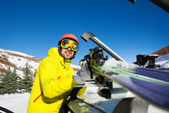 Active man fastening skis on the roof of car Royalty Free Stock Image