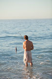 Active man fishing in the sea. Under the sun stock image