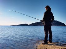 The active man is fishing on sea from the rocky coast. Fisherman check pushing bait. On the fishing line, prepare rod and than throw lure into peacefull water Stock Photography