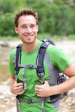 Active man portrait of sporty guy hiking outdoors. Young male hiker smiling happy at camera wearing backpack outdoors during hike in forest nature. Caucasian stock photo