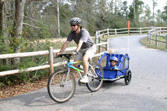 Active man pulling son on bike. Caucasian father and son enjoying a bike ride on a country bike trail Stock Images