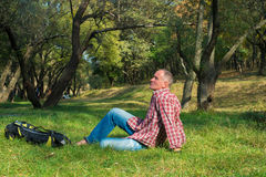 Active man relaxing  in the park in autumn sunny day. A man hiker with backpack lies  at green grass and enjoying life Stock Images