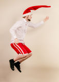 Active man in santa hat dancing and jumping. Stock Images