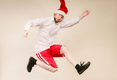 Active man in santa hat dancing and jumping. Stock Image