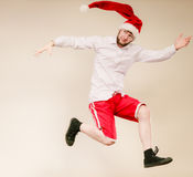Active man in santa hat dancing and jumping. Stock Image
