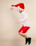 Active man in santa hat dancing and jumping. Royalty Free Stock Photos