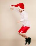 Active man in santa hat dancing and jumping. Royalty Free Stock Photos