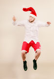 Active man in santa hat dancing and jumping. Stock Photos