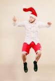Active man in santa hat dancing and jumping. Stock Photos
