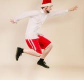Active man in santa hat dancing and jumping. Royalty Free Stock Image