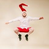 Active man in santa hat dancing and jumping. Stock Photo