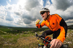 Active man sitting on bike and eating sandwich Royalty Free Stock Photography