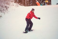 Active man snowboarder in red jacket riding on slope, snowboarding. Active man snowboarder in red jacket, riding on slope, snowboarding closeup Royalty Free Stock Photo