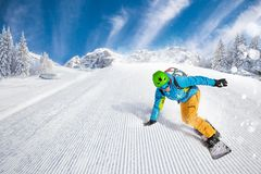 Man snowboarder riding on slope. Active man snowboarder riding on slope during beautiful sunny day in the ountains stock photography