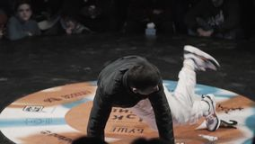 Active man in sportive dark clothes energetically breakdances at festival. Dynamic nice-looking young male wearing dark stylish sportive outfit is breakdancing stock video footage