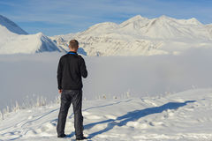 Active man is standing over mist in winter mountains Stock Photos