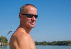 Active man in the sunglasses is relaxing at the cable park on th Royalty Free Stock Photography