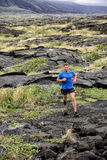 Active man trail running on volcanic rocks Stock Photos