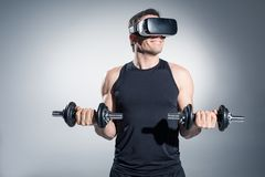 Active man training with dumbbells while wearing vr glasses. On grey background Royalty Free Stock Image