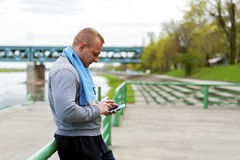 Active man using smartphone. In park Stock Images