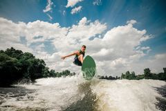 Active man wakesurfing on the board down the river against the cloudy sky and trees. Active man wakesurfing on the board down the river against the background of royalty free stock photos