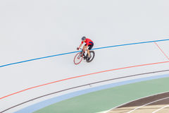 Active man on white velodrome outdoor. Sports man in a red T-shirt and a black bicycle Royalty Free Stock Photos