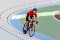 Active man on white velodrome outdoor. Sports man in a red T-shirt and a black bicycle Royalty Free Stock Photography