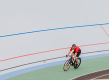 Active man on white velodrome outdoor. Sports man in a red T-shirt and a black bicycle Royalty Free Stock Images