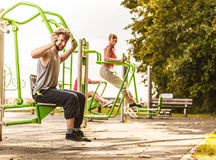 Active man and woman exercising at outdoor gym. Stock Photos
